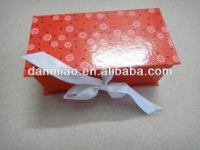 Red polka dot paper cardboard folded gift box with ribbon