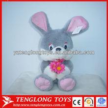 Cute sitting stuffed plush gray rabbit with flower