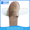Light brown disposable warm hotel slippers with gold embroidery