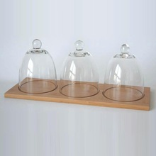 three clear cake dome on one wood plate