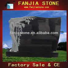 Black granite headstone with trees