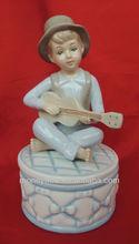 21-B A boy playing guitar on a musical box