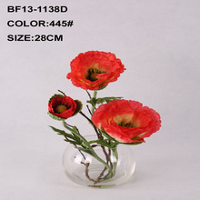 Red artificial poppy with acrylic water in glass pot