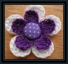 purple crochet flower with polka dot cover button