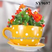 Ceramic yellow tea cup and saucer flower pot