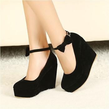 Очаровательные черные туфли на танкетке украшенные тонким ремешком с бантиком.