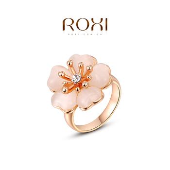 Roxi милое женское кольцо, изготовлено из розового золота с трех разовым золотым напылением, выгровировка в виде цветка посредине, украшенная яркими австрийским кристаллом, высокое качество